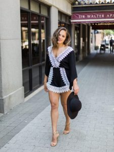 Woman in a black and white romper with black hat. Black and white photo of woman in a romper. Styled by Chic and Classy Image Consulting.