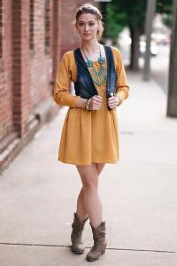 Woman in mustard dress and brown boots with short jean vest. Styled by Khalilah Jones of Chic and Classy Image Consulting